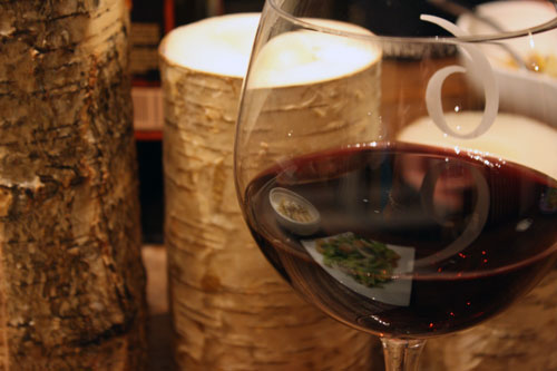 red wine in a glass next to tree bark candles