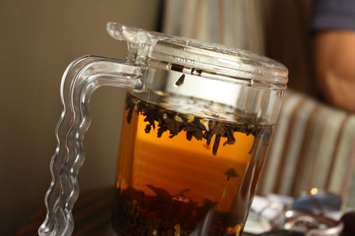 clear tea pot with orange tea and tea leaves