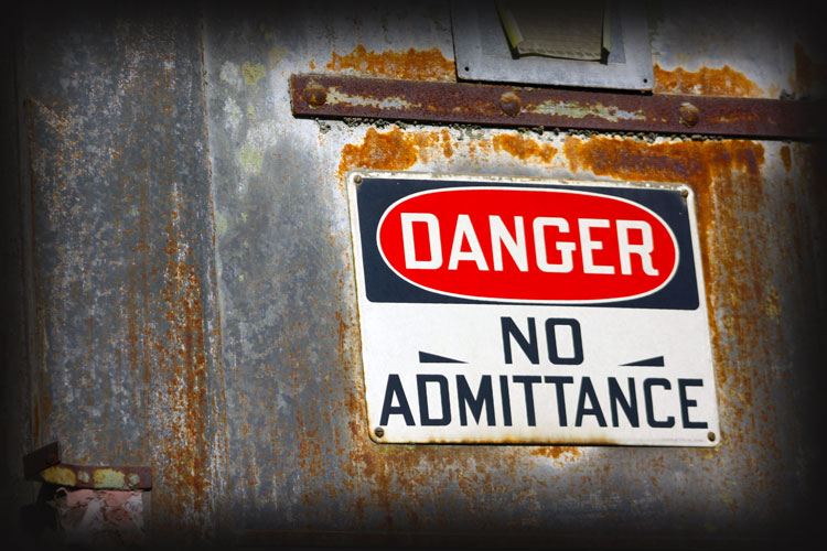 rusty danger no admittance sign on steel building