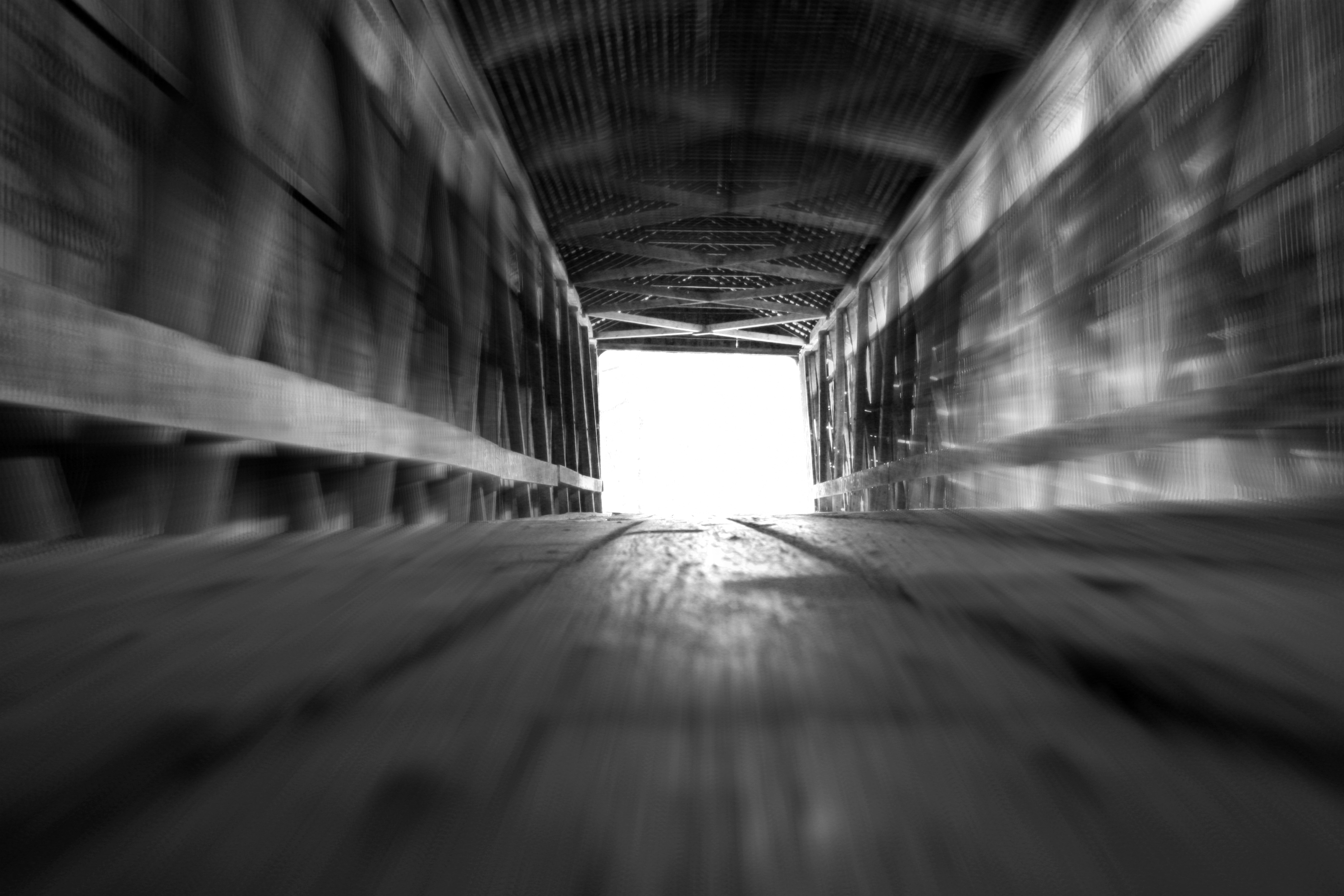 black and white light at the end of the tunnel on a covered bridge