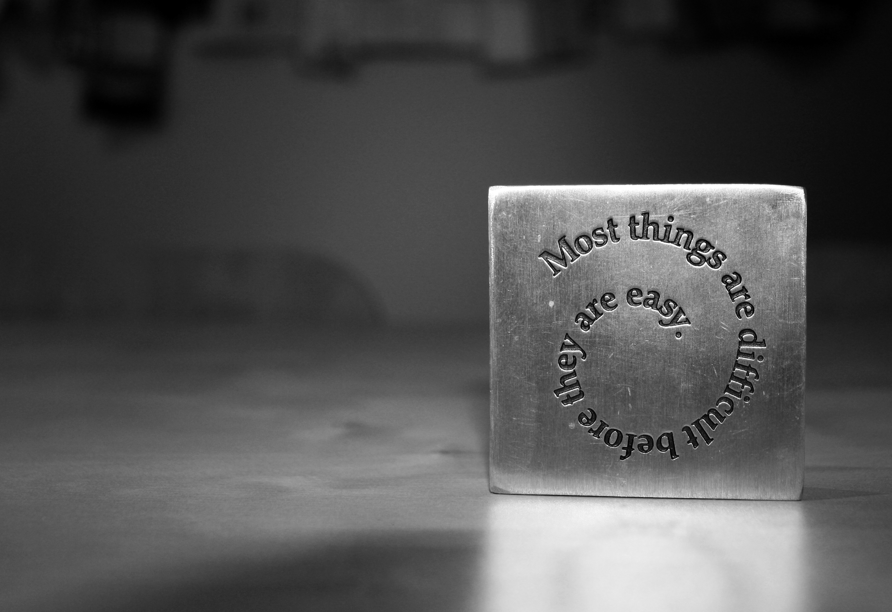 """silver square paperweight inscribed """"most things are difficult before they are easy"""""""