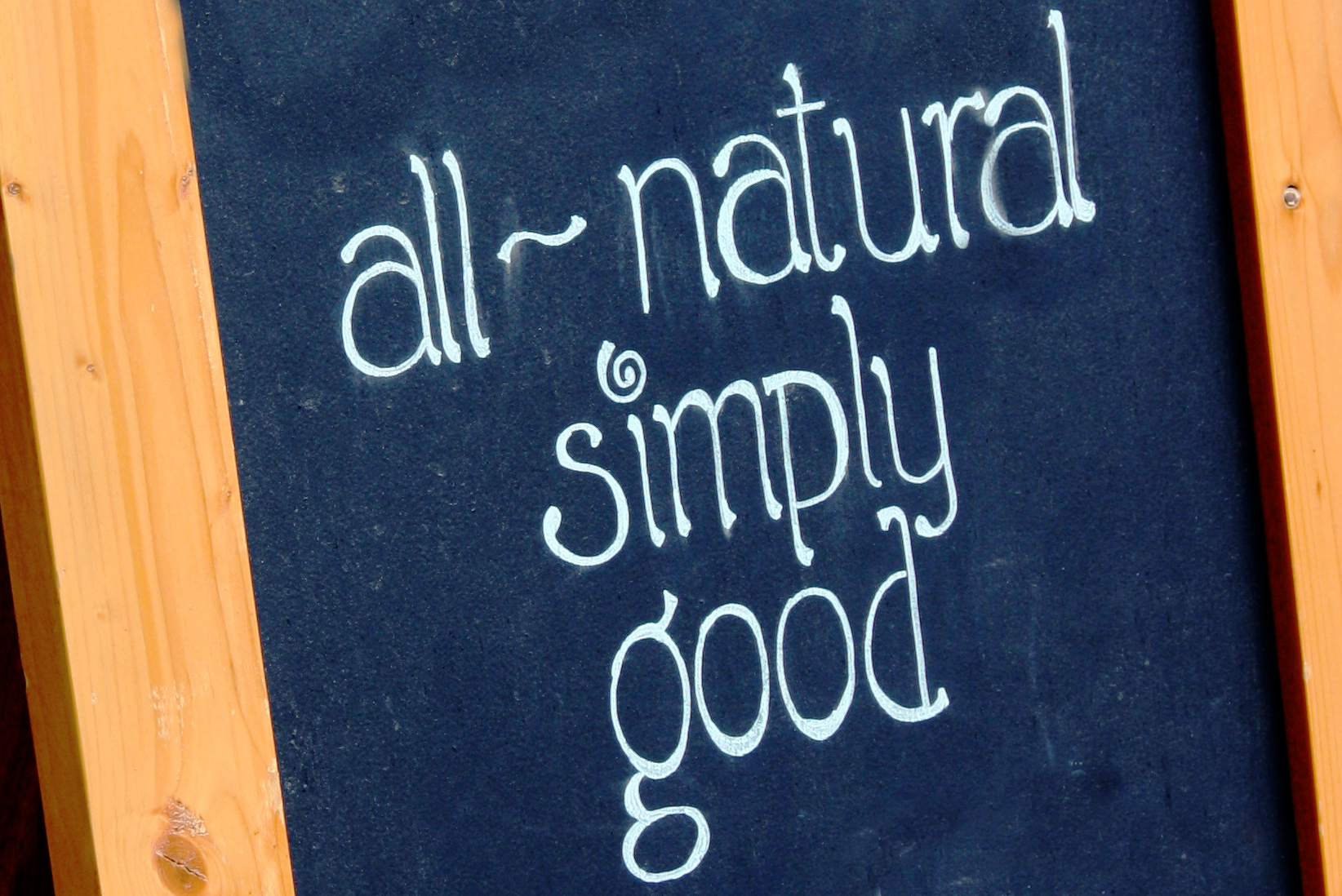 """chalkboard that states """"all natural simply good"""" in white writing"""